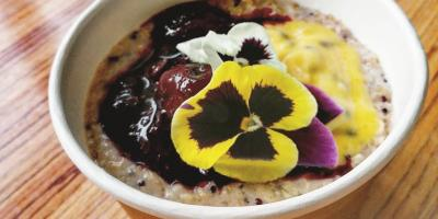 Quinoa oat and cinnamon porridge topped with Berry compote and passion fruit curd